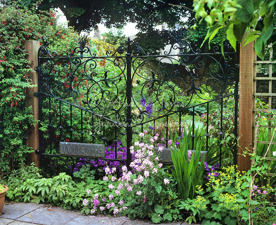 (Double)   Ornate metal gates with flowering perennials in St Andrews Preservation Trust Museum Garden, St Andrews, Scotland