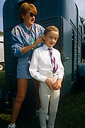 "Behind their horsebox, a dedicated mother puts the finishing touches to her daughter's hair at a gymkhana in Cheltenham, Gloucestershire. Wearing regulation jodhpurs, tie and hairnet, the young girl is almost ready to mount her pony and hopefully earn winning rosettes. The word gymkhana is an Indian Raj term that referred to a place where sporting events took place to test the skill of the competitors. In the UK and east coast of the US, the term gymkhana now almost always refers to an equestrian event for riders on horses, often with the emphasis on children's participation (such as those organised here by the Pony Club). Gymkhana classes include timed speed events such as barrel racing, keyhole, keg race (also known as ""down and back""), flag race, and pole bending."