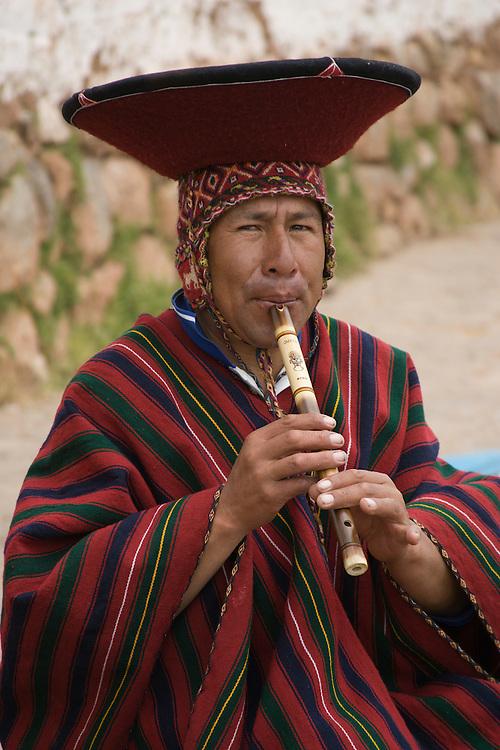 Flute seller playing flute in market, Chinchero (near Cuzco), Peru, South America