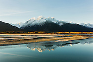 Sunrise and reflection of the Chilkat Mountains on the Chilkat River in the Chilkat Bald Eagle Preserve near Haines in Southeast Alaska. Winter. Morning.