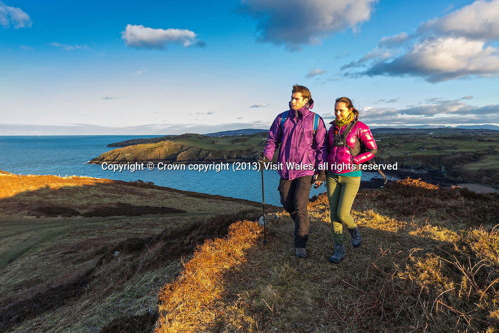 Couple walking above Porth Wen at sunset<br /> Near Amlwch<br /> Wales Coast Path<br /> Anglesey<br /> North<br /> Walking<br /> Activities and Sports