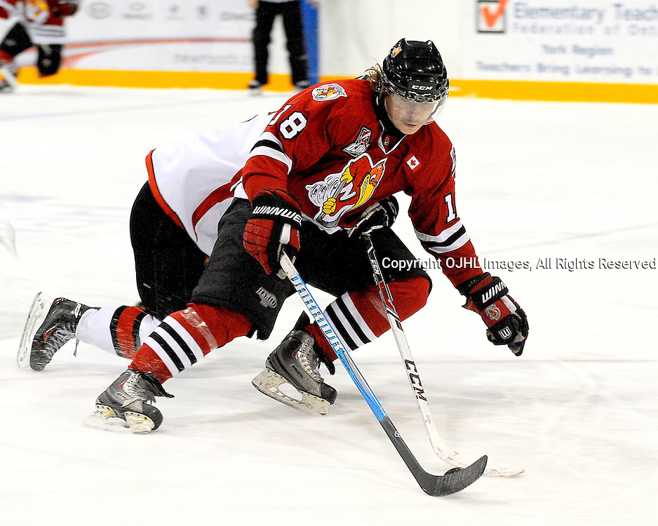 NEWMARKET, ON - Nov 14 : Ontario Junior Hockey League Game Action between the Newmarket Hurricanes Hockey Club and the Stouffville Spirit Hockey Club. Nic Coric #18  of the Newmarket Hurricanes Hockey Club tries to get the puck while being checked.<br /> (Photo by Phillip Sutherland / OJHL Images)