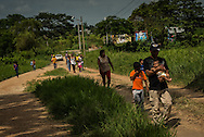 TENOSIQUE, MEXICO - JULY 2, 2014:  Undocumented migrants walk to a shelter in Tenosique after a train passed by.  Broke, exhausted, daunted by the perilous journey and increasingly confused over the chances for legal admission to the United States, more and more migrants with children are taking a long pause in Mexico, where they find a porous southern border that allows easy entre, a network of shelters to support them and a government that swings between crackdown and compassion in its treatment of those without authorization on its soil. PHOTO:  Meridith Kohut for The New York Times