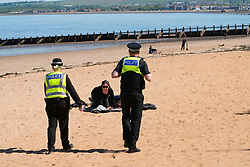 Portobello, Scotland, UK. 11 May 2020. Police patrolling promenade and beach at Portobello this afternoon in warm sunny weather. They spoke to the public who were sitting on the beach or on sea wall asking them to keep moving. Iain Masterton/Alamy Live News