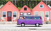 A man drives a purple Volkswagon van down a road in front of a row of pink houses in Oceanside, Calif., on Aug. 3, 2014.