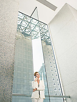 Businesswoman using mobile phone in office building (low angle view)