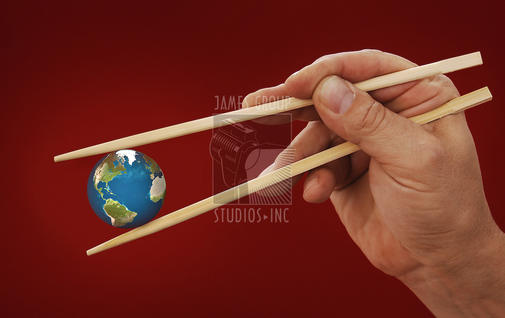 hand holding the earth between two chopsticks on Chinese red background