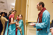 Baltimore, Maryland - December 20, 2014: The flower girls at Trisha Satya Pasricha and Eshwan Ramudu wedding are negotiating a price with the best man for the return of the groom's shoes, which are hidden in their sarees. Shoes are not allowed in the mandap, the traditional Hindu wedding structure, and it is customary after the ceremony for children to ransom the shoes. Karli Khanna-Reichert, 12, from Princeton Junction, NJ, left, and Olivia Sherwin, 9, from Essex Junction, Vermont, started negotiations at $1500. Best Man Alex Bick eventually procured the shoes for $150. <br /> <br /> CREDIT: Matt Roth for The New York Times<br /> Assignment ID: 30168620A