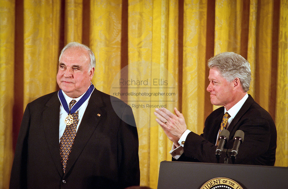 President Bill Clinton applauds former German Chancellor Helmut Kohl after presenting him with the Medal of Freedom at the White House April 20, 1999. Kohl received the medal for his many years of good relations with the U.S and is the first foreigner to receive the honor since 1991.