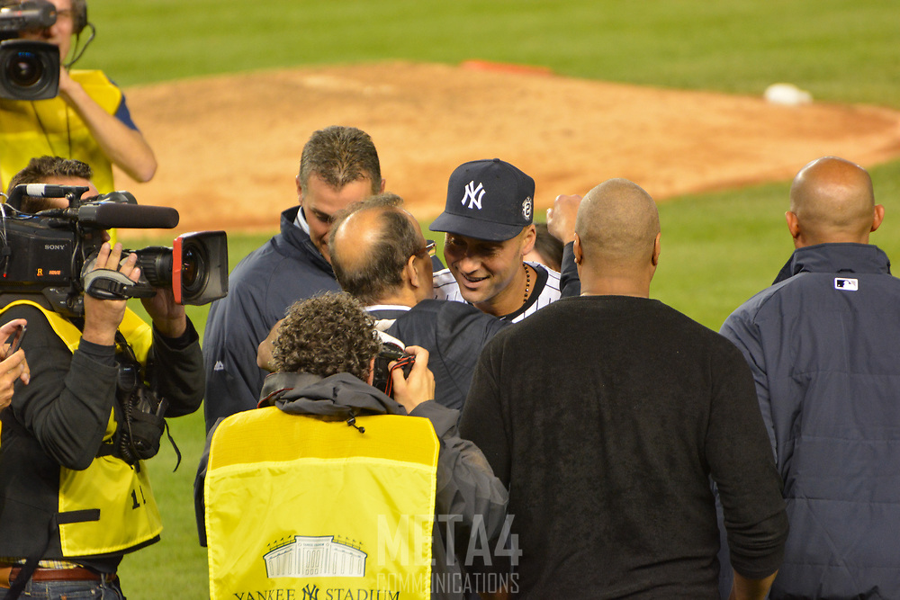 Derek Jeter is hugged by manager Joe Torre and joined by teammates (l.-r.) Andy Pettitte, Bernie Williams and Mariano Rivera.