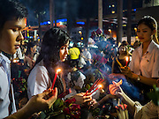 18 FEBRUARY 2016 - BANGKOK, THAILAND:  College students light their incense before praying for love at the Trimurti Shrine in Bangkok. Every Thursday night, starting just after sunset and peaking at 21.30, hundreds of Bangkok single people, or couples seeking guidance and validation, come to the Trimurti Shrine at the northeast corner of Central World, a large Bangkok shopping mall, to pray to Lord Trimurti, who represents the trinity of Hindu gods - Brahma, Vishnu and Shiva. Worshippers normally bring an offering of red flowers, fruits, one red candle and nine incense sticks. It's believed that Lord Trimurti descends from the heavens at 21.30 on Thursday to listen to people's prayers. Although most Thais are Buddhists, several Hindu traditions have been incorporated into modern Thai Buddhism, including reverance for Trimurti.      PHOTO BY JACK KURTZ