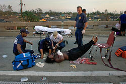 29 August, 2005. New Orleans, Louisiana.<br /> Hurricane Katrina hits New Orleans. Rescue workers frantically search for survivors in the rising flood waters of the 9th ward, bringing them to relevant safety on the elevated section of I-10. Residents of the 9th ward rescued from submerged homes are immediately transported onto Interstate 10 and waiting paramedics.<br /> Photo; Charlie Varley.