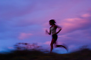 A young woman running across a field at sunset on the Boulder Vally Ranch trail near Boulder, Colorado