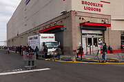 Brooklyn, NY - 7 April 2020. By 9:30 AM, the line to enter the grocery and warehouse store Costco on 3rd Avenue already stretches across the front of the building and West along the length of the South side back to 2d Avenue, North across the back of the store, East across the North side of the store, and continues to wrap again around the front to the entrance. This part of the line is on the South side of the store. The store opens from 8 to 9 AM on Tuesdays through Thursdays for customers over 60, but some customers under 60 were seen waiting before 8.