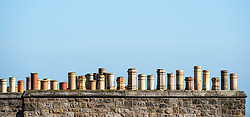 Row of old chimney pots on a house in Edinburgh, Scotland, United Kingdom