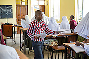 A young male local teacher talking to students during a geography class. He is being monitored by VSO volunteer Paul Jennings and local teacher Rebecca Ngovano. Rebecca has been working with VSO volunteer Paul Jennings for over 6 months to improve teaching methodologies in classrooms. Angaza school, Lindi, Tanzania