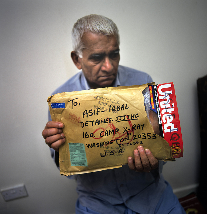 Mohamed Iqbal, 70, from Tipton, Birmingham, father of Asif Iqbal, 20 who was captured in Afghanistan in 2001 and accused of fighting for the Taliban. Mohamed is seen holding copies of football magazines that he sent to his son but which were returned undelivered. Asif is being detained by the US at the Guantanamo Bay military base at the edge of Cuba. Photographed at the family home in Tipton in the East Midlands, UK.