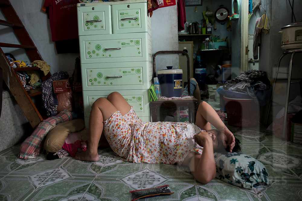 A Vietnamese woman takes rest on the floor of her dwelling, Ho Chi Minh City, Vietnam, Southeast Asia