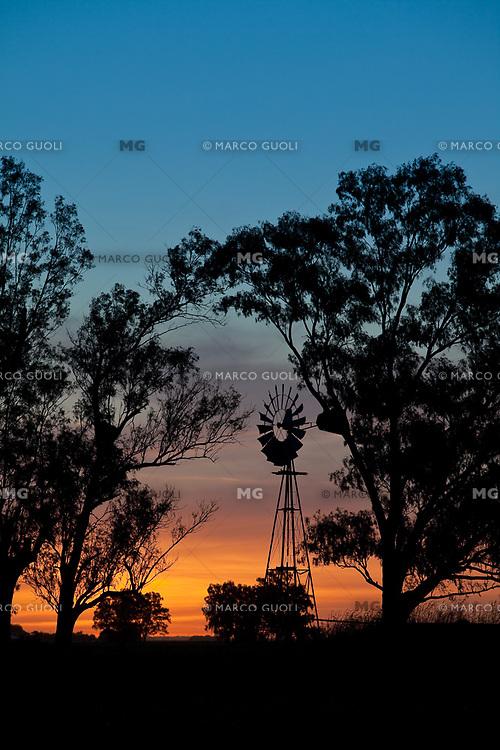 SILUETA DE UN MOLINO DE AGUA ENTRE ARBOLES AL ATARDECER, TRES SARGENTOS, PROVINCIA DE BUENOS AIRES, ARGENTINA (PHOTO BY MARCO GUOLI)
