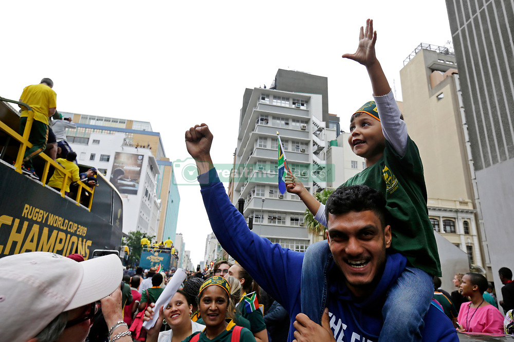 Monday 11th November 2019.<br /> City Hall, Grand Parade,<br /> And City Centre, Cape Town,<br /> Western Cape,<br /> South Africa.<br /> <br /> SPRINGBOKS CELEBRATE WINNING THE RUGBY WORLD CUP CHAMPIONSHIP IN 2019 WITH A COUNTRYWIDE VICTORY TOUR!<br /> <br /> SPRINGBOKS RUGBY WORLD CUP VICTORY TOUR CAPE TOWN!<br /> <br /> A young boy sits on top of his father's shoulders as they watch along with other excited fans as they celebrate the Springboks driving past in their open top bus in the Cape Town City Centre.<br /> <br /> The reigning Rugby World Cup Champions namely the South African Springbok Rugby Team, celebrates winning the Webb Ellis Cup during the International Rugby Football Board Rugby World Cup Championship held in Japan in 2019 with their Victory Tour that culminated in the final city tour taking place in Cape Town. Thousands of South African fans filled the streets of the city all trying their best to show their support for their beloved Springboks and to celebrate them winning the Rugby World Cup for the third time. South Africa previously won the Rugby World Cup in 1995, 2007 and now again in 2019. South African Springbok Captan Siya Kolisi took the opportunity to speak to the gathered crowd about how something like this brings unity and that we should live together as a nation that practices what is known as ubuntu. Ubuntu is a quality that includes the essential human virtues of compassion and humanity. This image taken in Cape Town on Monday 11th November 2019.<br /> <br /> This image is the property of Seven Bang Media Group (Pty) Ltd, hereinafter referred to as SBM.<br /> <br /> Picture By: SBM / Mark Wessels. (11/11/2019).<br /> +27 (0)61 547 2729<br /> mark@sevenbang.com<br /> www.sevnbang.com<br /> <br /> Copyright © SBM. All Rights Reserved.
