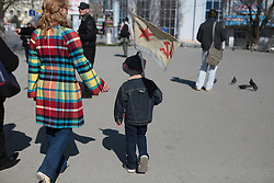 Crimea one day before the referendum. A young child walks in the street with a soviet flag. Simferopol, . Saturday, 15th March 2014. Picture by Daniel Leal-Olivas / i-Images
