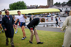 © Licensed to London News Pictures. 28/06/2017. London, UK. A spectator ducks underneath a boat as it is carried form the water on day one of the Henley Royal Regatta, set on the River Thames by the town of Henley-on-Thames in England.  Established in 1839, the five day international rowing event, raced over a course of 2,112 meters (1 mile 550 yards), is considered an important part of the English social season. Photo credit: Ben Cawthra/LNP