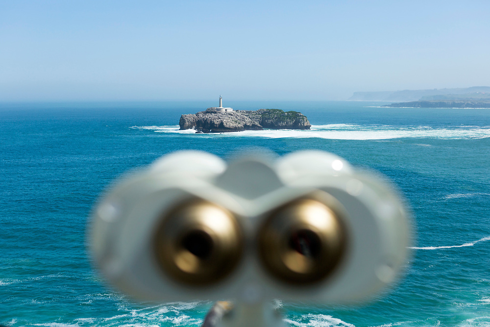 SANTANDER, SPAIN - April 18 2018 -  Pay for view binoculars look out on to a sea view of the Bay of Santander and Mouro Island & lighthouse on a sunny day, Cantabria, Northern Spain, Europe.