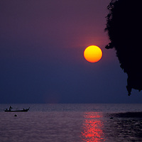 Longtail fishing boat silhouetted against setting sun, Rae Leh Beach, Thailand
