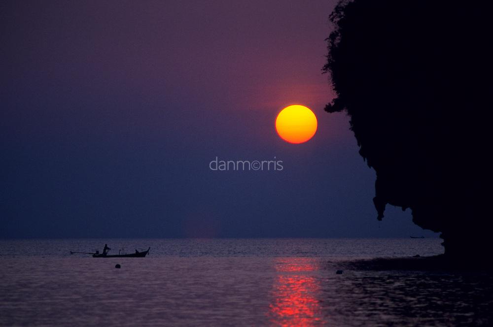 Longtail fishing boat silhouetted against setting sun, Rae Leh Beach, Thailand