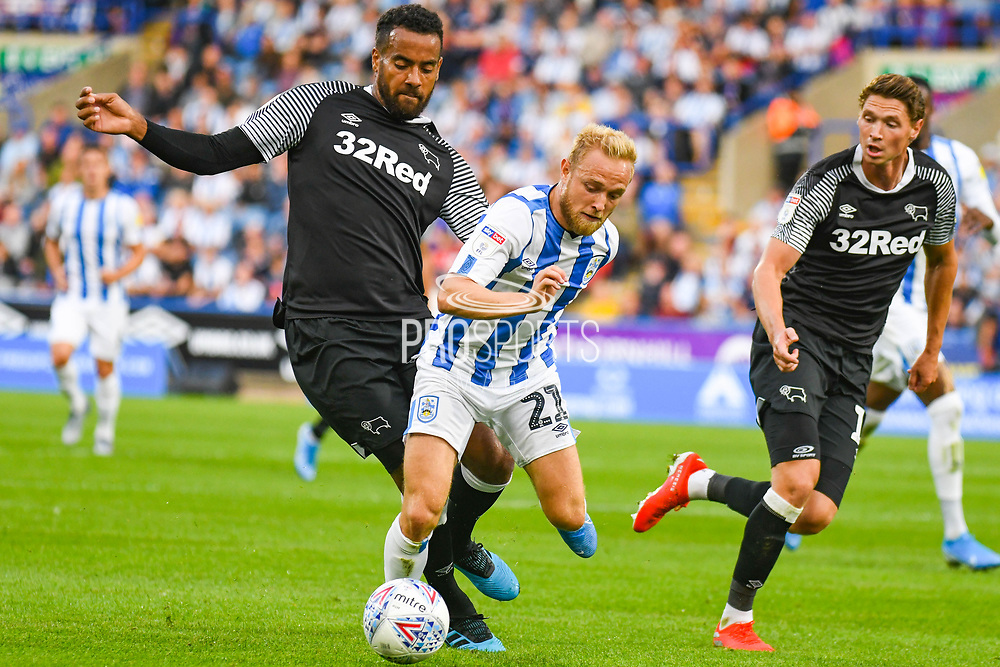 Tom Huddlestone of Derby County (44) and Alex Pritchard of Huddersfield Town (21) in action during the EFL Sky Bet Championship match between Huddersfield Town and Derby County at the John Smiths Stadium, Huddersfield, England on 5 August 2019.