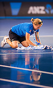 An Australian Open tournament official is reflected as she mops rainwater from the center court at Rod Laver Arena in Melbourne. A shower deluged the venue for a few minutes before the arena roof could be slowly closed.