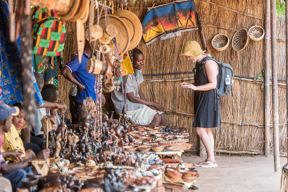 Young woman tourist browses over table full of handcrafted souvenirs while vendor assists her with purchase, Mukuni Village, Zambia