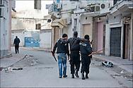 Un policier blessé lors des affrontements est évacué par un habitant et un policier à proximité de la Medina. // A la suite de nombreux pillages et saccages commis dans le centre ville de Tunis la Police accompagnée des habitants organisés en comité de quartiers chassent les pilleurs, Tunis dimanche 27 février 2011. © Benjamin Girette/IP3 press