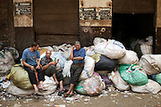 Christians Copts sit on garbage sacks in garbage city, Cairo.<br />