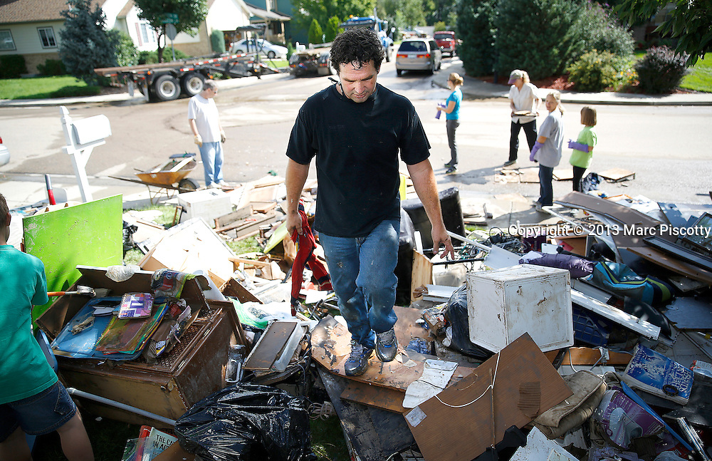 LONGMONT, CO - SEPTEMBER 16: Michael Cruz of Longmont, Colorado helps a neighbor dispose of flood damaged items as residents clean up in the wake a week of heavy flooding on September 16, 2013. (Photo by Marc Piscotty/ © 2013)