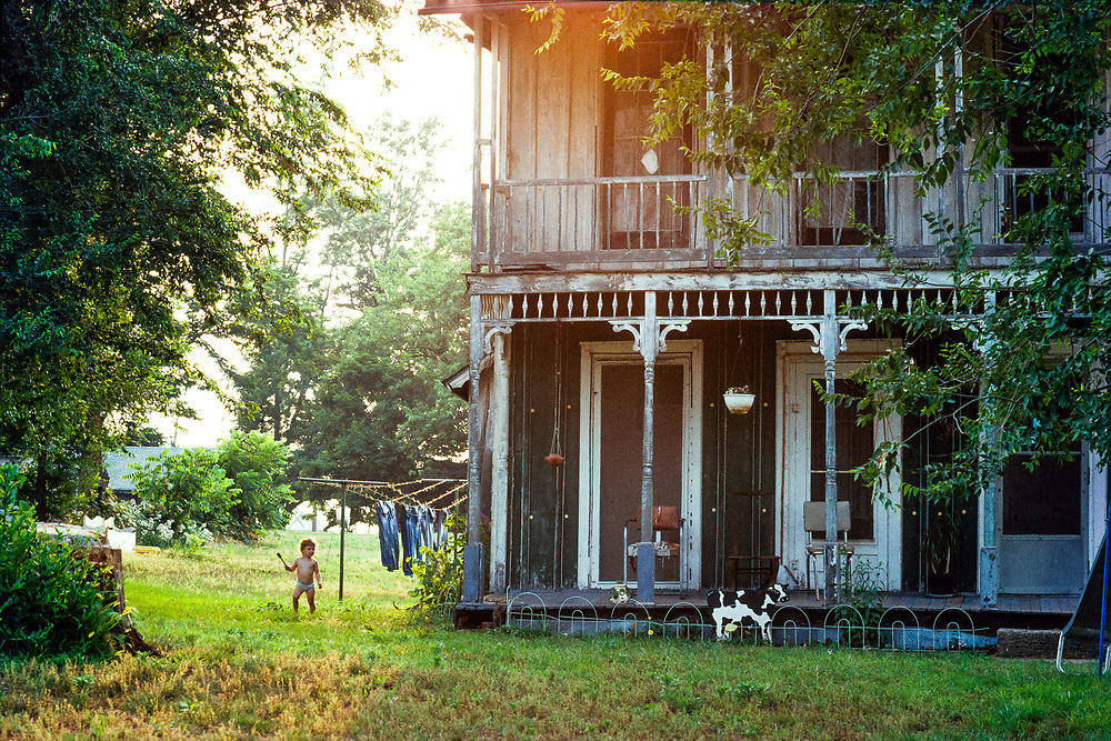 Small child in a yard near hanging laundry at sunset in Naples, Illinois