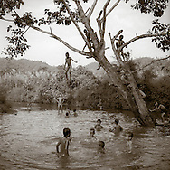 Village boys play in a swimming hole - launching off a tree for jumping in, Northern Thailand.