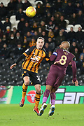 Hull City midfielder Jackson Irvine (16) and Swansea City midfielder Leroy Fer (8) battle for the ball in the air during the EFL Sky Bet Championship match between Hull City and Swansea City at the KCOM Stadium, Kingston upon Hull, England on 22 December 2018.
