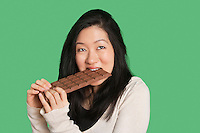 Cute young woman eating a large chocolate bar over green background