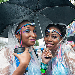© Licensed to London News Pictures. 31/08/2015. London, UK. Dancers shelter under an umbrella as revellers and dancers brave the heavy rain to take part in Notting Hill Carnival, Europe's biggest Caribbean festival. Photo credit : Stephen Chung/LNP