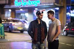"""© Licensed to London News Pictures . Manchester , UK . 05/04/2015 . A man wearing pink rabbit ears talks to a second man , opposite """" The Birdcage """" nightclub in central Manchester . Revellers on a Saturday night out during the Easter Bank Holiday weekend . Photo credit : Joel Goodman/LNP"""