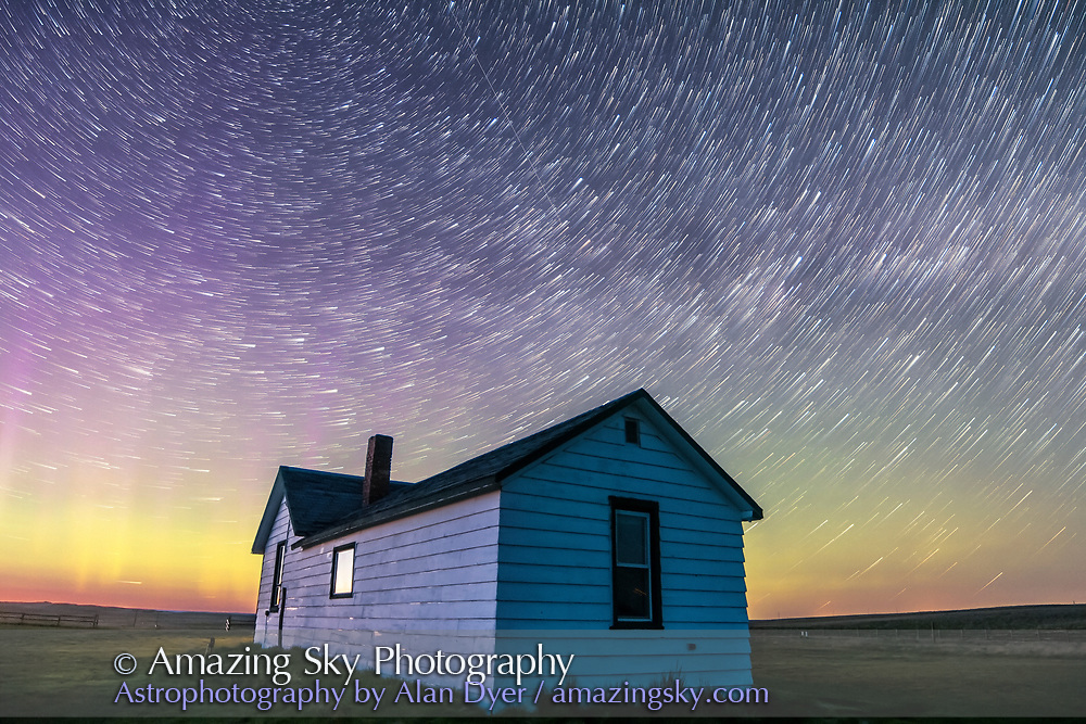 Circumpolar star trails at dawn over the historic Butala homestead at the Old Man on His Back Prairie and Heritage Conservation Area in southwest Saskatchewan, taken May 2015. This is a stack of 70 frames from a larger time-lapse sequence, from the start of the sequence in the dusk twilight, with some aurora active and adding green and magenta to the sky. Cassiopeia is at left over the house. <br /> <br /> Each exposure is 40 seconds with the 14mm lens at f/2.8 and Canon 60Da at ISO 1600. Stacked with Advanced Stacker Actions, Comet effect. The foreground comes from a stack of 8 of the first exposures, mean combined, to smooth noise.