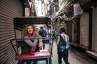 A female tourist on a bicycle rickshaw posing for a picture in Chandni Chowk, one of India's largest wholesale markets in Delhi.