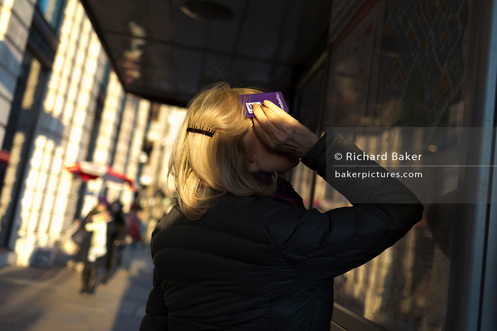 A lady uses her Freedom Pass holder to shield her eyes from winter sunshine at a bus stop on Piccadilly, on 20th January 2020, in London, England.