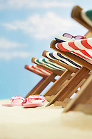 Row of deck chairs on beach focus on flip-flops on ground