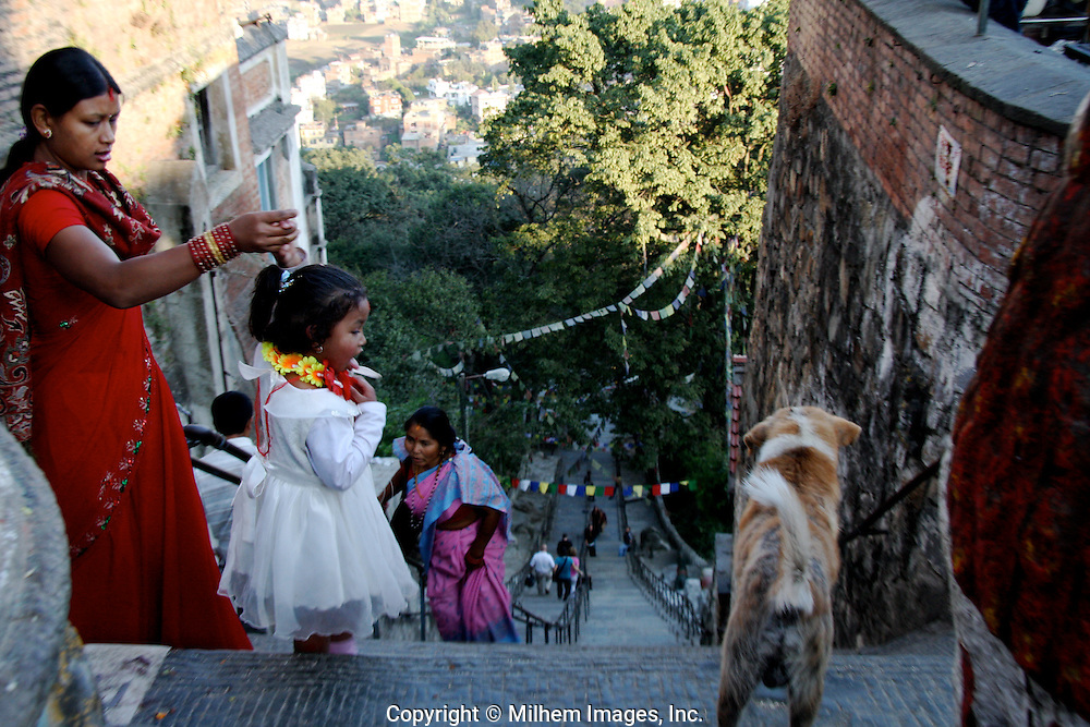 Local residents visit the famous Katmandu Buddhist temple to pay homage to Buddha.