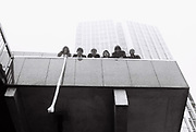 Six teenage friends look down form building on London Wall, London. London, UK, 1980s.