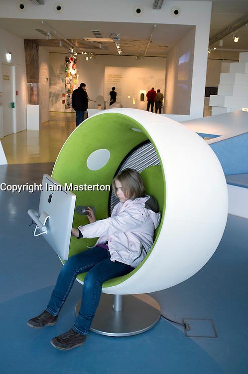 Young girl visitor using multimedia area of Humboldt Box visitors center at Lustgarten on Unter den Linden Mitte Berlin