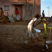A girl is lifted off the ground as she pumps water from a well in Nagappattinam, on the tsunami-hit southeastern coast of India..The December 26, 2004 tsunami killed thousands of people along this coast, smashing boats, roads and houses and tearing thousands of families apart. .Picture taken February 2005 in Nagapptinam, Tamil Nadu, India, by Justin Jin