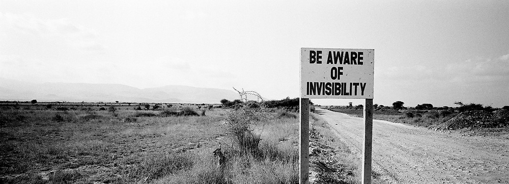 Beware of Invisibility sign in empty landscape